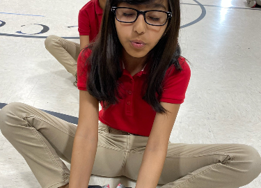 A student practices a yoga pose with her legs crossed and her eyes closed