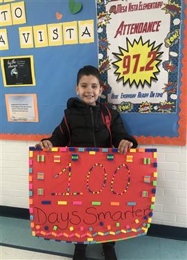 Mesa Vista student holding a sign celebrating the 100 days of school.