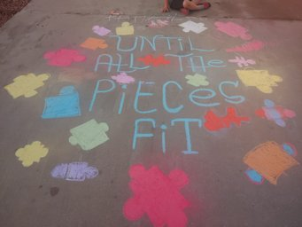 Autism awareness puzzle chalked on a sidewalk.