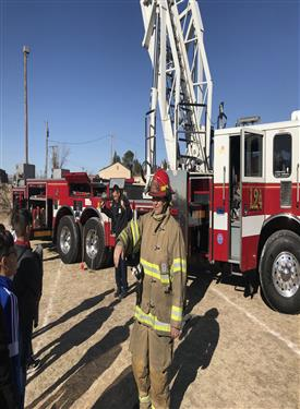 A firefighter talks about his equipment in front of the fire engine.