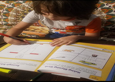 A student is working in his workbook.