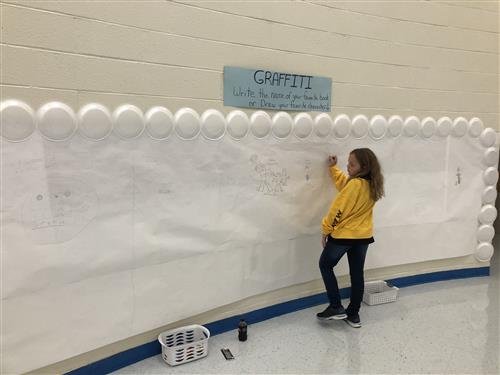Student participates on the graffiti wall
