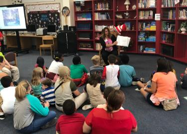 Principal reads aloud book to students