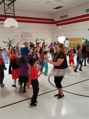 Teachers dance with the students.