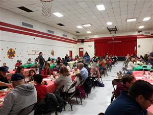 TPresa gym with tables filled with families enjoying lunch together