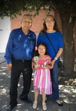 Grandparents celebrating award with granddaughter