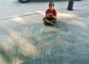Student sitting by chalked sidewalk saying thank you