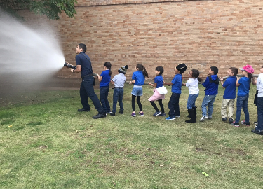 Fireman and students using the fire hose outside