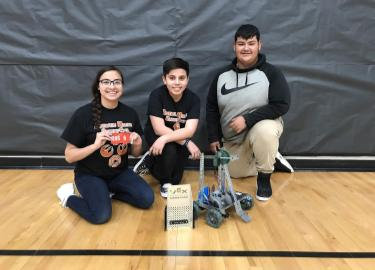 Winning Rebel Robotics team poses with trophy and robot.