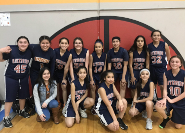 7th Grade Lady Rebels basketball team poses for picture after win.