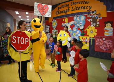 Students walking in parade with stop signs & Mr. Happy.