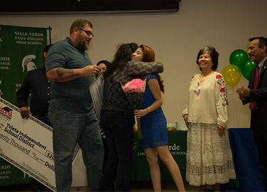 Parent hugging child as she is awarded scholarship